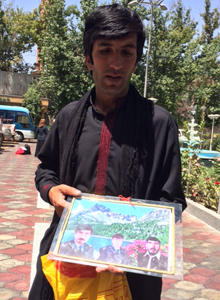 Muhammad Saber holds a photo in Kabul, Aug. 11, 2014, showing his brothers, who were killed in a U.S. and Afghan forces raid on his home in Paktia province