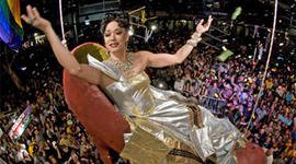 """""""Sushi,"""" portrayed by female impersonator Gary Marion, dangles high above New Year's Eve revelers in a giant reproduction of a woman's high heel at the Bourbon Street Pub late Friday, Dec. 31, 2010, in Key West, Fla."""