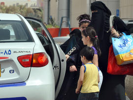 Saudi woman gets into a taxi with her children