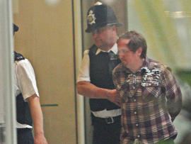 A man, named on Twitter as Jonnie Marbles, is led from Portcullis House in London, Tuesday July 19, 2011, following an incident as Rupert Murdoch and James Murdoch gave evidence before a House of Commons Committee on the News of the World phone hacking scandal.