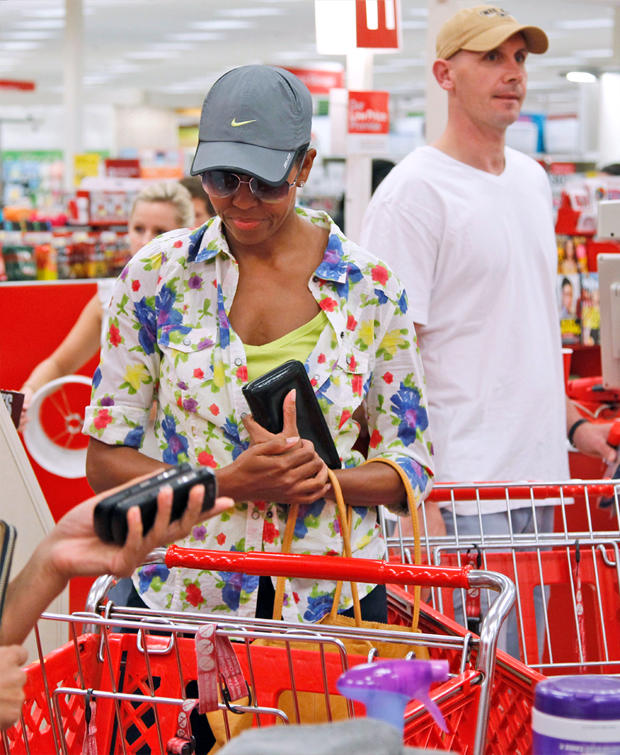 First lady Michelle Obama, wearing a hat and sunglasses, stands in line at a Target department store in Alexandria, Va., Thursday, Sept. 29, 2011, after doing some shopping.