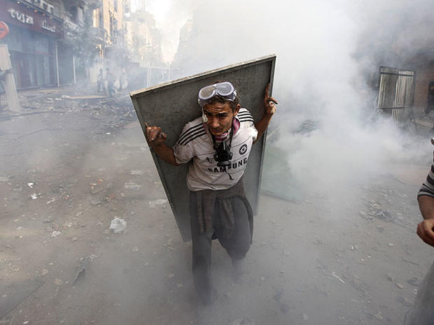 An Egyptian protester using scrap metal as a shield takes cover from tear gas during clashes with security forces near Tahrir Square in Cairo, Egypt, Nov. 23, 2011.