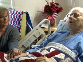 Barbara Stadler, a Veterans Affair employee who volunteers at the hospital's end-of-life program, holds the hand of Korean war vet Richard Murley.