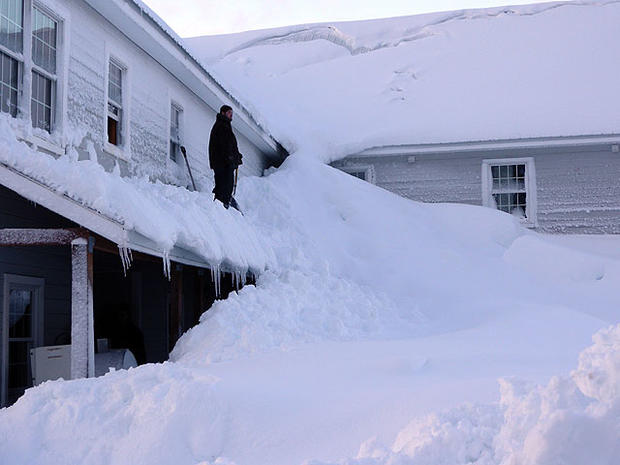 在2012年1月7日星期六,阿拉斯加州国土安全和紧急事务管理处提供的照片中,一名男子站在阿拉斯加科尔多瓦渔镇的一座被雪覆盖的房子里。