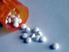 A closeup of some pills pouring out of a prescription bottle.