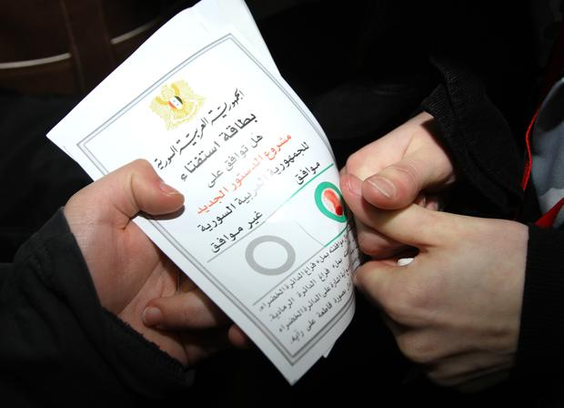 A Syrian citizen marks a ballot paper with her blood at a polling station during a referendum on the new constitution, in Damascus, Syria, on Sunday Feb. 26, 2012.