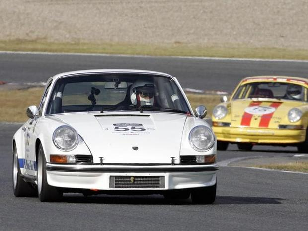 MINE, JAPAN: Japanese driver Junichi Yamano drives his 1973 Porsche 911 Carrera RS (L) leading a 1971 Porsche 911T (R) during the second round class 3 and 4 race of the Le Mans Classic Japan 2005 at the Mine circuit in Mine, Yamaguchi prefecture, 30 October 2005. Yamano won the class 4 category. AFP PHOTO / TOSHIFUMI KITAMURA (Photo credit should read TOSHIFUMI KITAMURA/AFP/Getty Images)