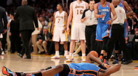 James Harden lies on the floor after being hit by Metta World Peace