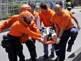 Emergency personnel assist an injured person after an explosion ripped through a crowded area of Bogota, Colombia, May 15, 2012.
