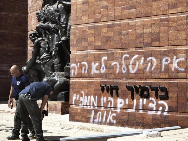 Police inspect anti-Zionist graffitit on the Yad Vashem memorial