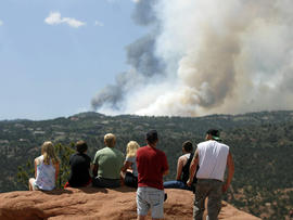 People watch as smoke billows from a wildfire west of Colorado Springs, Colo. on Saturday, June 23, 2012.