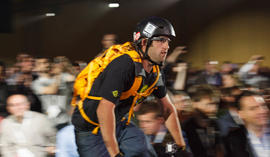 A bicyclist rides down the aisle at Google I/O wearing Project Glass computerized glasses.