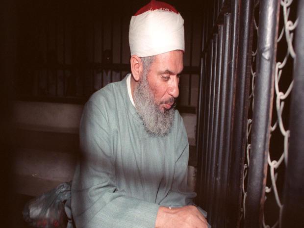 """""""盲目的酋长""""奥马尔艾哈迈德拉赫曼于1989年8月6日在开罗开庭时坐在铁笼内祈祷。"""