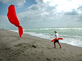 A lifeguard walks on Hallandale Beach in Florida on a windy day.