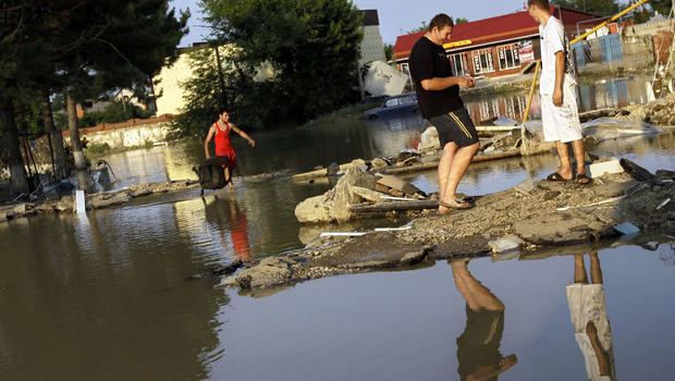People walk along a flooded street in Krimsk, about 1,200 kilometers (750 miles) south of Moscow, Sunday July 8, 2012.
