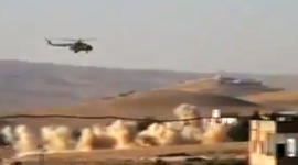 This citizen journalism image provided by Shaam News Network SNN, taken on Tuesday, July 24, 2012, purports to show a helicopter gunship flying a bombing run in al-Qalmoun, Syria.