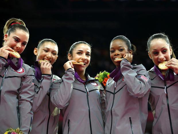 U.S. gymnasts McKayla Maroney, Kyla Ross, Alexandra Raisman, Gabrielle Douglas and Jordyn Wieber bite their gold medals at the artistic gymnastics women's team final at the 2012 Summer Olympics July 31, 2012, in London.
