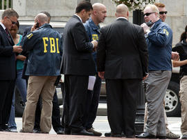 Washington police and FBI agents gather outside the Family Research Council in Washington Aug. 15, 2012, after a security guard at the lobbying group was shot in the arm.