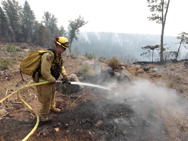 Firefighter Josh Gillick hoses down a hot spot of the Ponderosa Fire near Viola, Calif., Monday, Aug. 20, 2012. More than 1,400 fire fighters are battling the fire that has destroyed seven homes, burned 23 square miles.