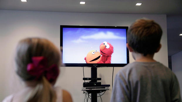 "In this Sept. 5, 2012, photo, from left, Zoe Shyba, 3, and Aidan Lain, 7, play ""Kinect Sesame Street TV"" at the Sesame Street Workshop in New York. ""Kinect Sesame Street TV"", launching Tuesday, Sept. 18, 2012, uses Kinect, a motion and voice-sensing controller created by Microsoft, to give Elmo, Big Bird and the rest of the Sesame Street crew a chance to have a real two-way conversation with their pint-sized audience. The effort represents the next step in the evolution of television, adding an interactive element to what's still largely a passive, lean-back experience."