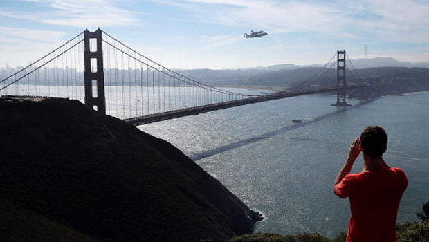 A spectator takes a photo of the Space Shuttle Endavour as it flies on top of a modified 747 jumbo jet over the Golden Gate Bridge while traveling to Los Angeles on September 21, 2012 in Sausalito, California. The Space Shuttle Endeavour did a 4-1/2 hour tour over California landmarks before heading to Los Angeles International Airport where it will be prepared to be moved to its new permanent home at the California Science Center in downtown Los Angeles. The shuttle will be on public display starting October 30. (Photo by Justin Sullivan/Getty Images)