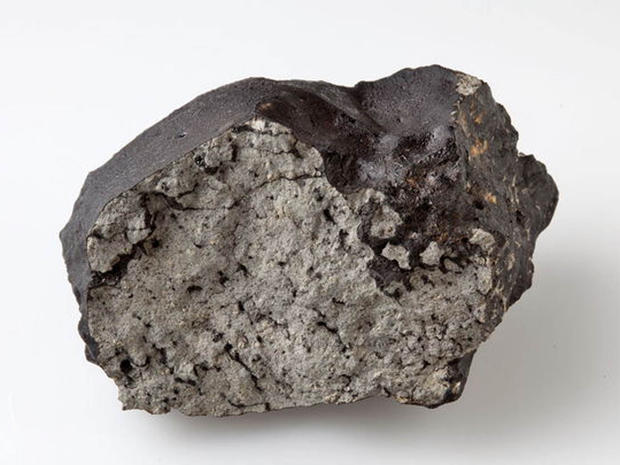 The 1.1 kg stone of the Tissint Martian meteorite at the Natural History Museum, London. The stone has a glossy black fusion crust. The fresh interior shows the large yellow/green olivine macrocrysts and pockets of black glass