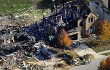 Citizens Energy workers continue their investigation Nov. 12, 2012, at the site of an explosion at a house in Indianapolis.