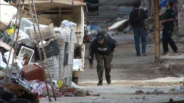 A Syrian ducks while passing through a dangerous part of Baba Amr in Homs, Syria.