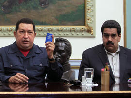 """In this Dec. 8, 2012, file photo released by Miraflores Press Office, Venezuela's President Hugo Chavez, left, holds up a copy of the Venezuelan national constitution as his Vice President Nicolas Maduro looks on during a televised speech at Miraflores presidential palace in Caracas, Venezuela. Chavez has suffered """"new complications"""" following his cancer surgery in Cuba, Maduro said Sunday, Dec. 30, 2012, describing the Venezuelan leader's condition as delicate."""