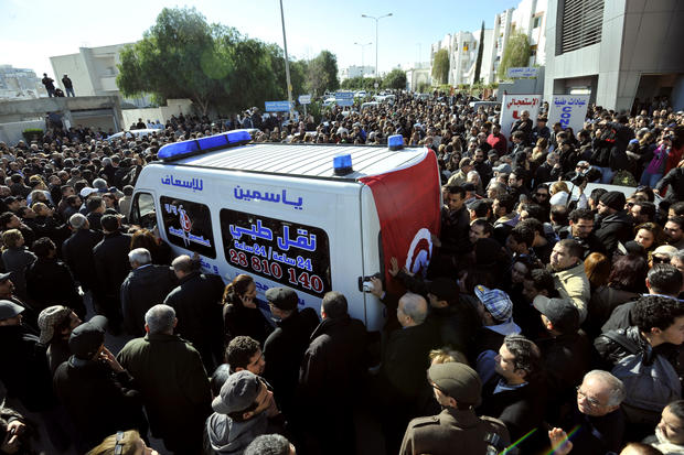 People surround an ambulance transporting the body of Chokri Belaid in Tunis