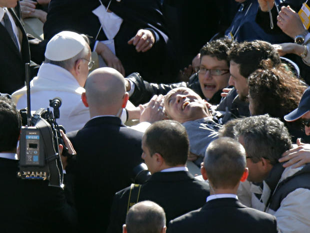 Pope Francis blesses a disabled man prior to his inaugural Mass