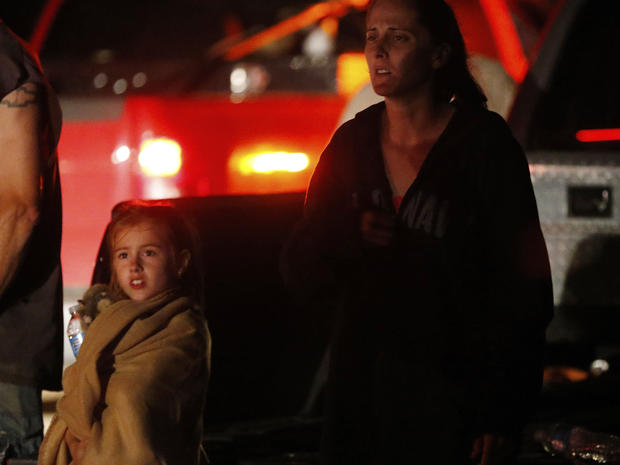 Seven-year-old Katrina Ash watches with her mother, Amber Ash, as heavy equipment is brought into their tornado damaged neighborhood