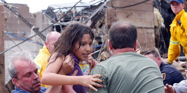 A child is pulled from the rubble of the Plaza Towers Elementary School in Moore, Okla., and passed along to rescuers Monday, May 20, 2013. A tornado as much as a mile (1.6 kilometers) wide with winds up to 200 mph (320 kph) roared through the Oklahoma City suburbs Monday, flattening entire neighborhoods, setting buildings on fire and landing a direct blow on an elementary school.
