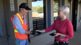 A woman shakes hands with Ric Ryan after donating money to UCLA's Operation Mend.