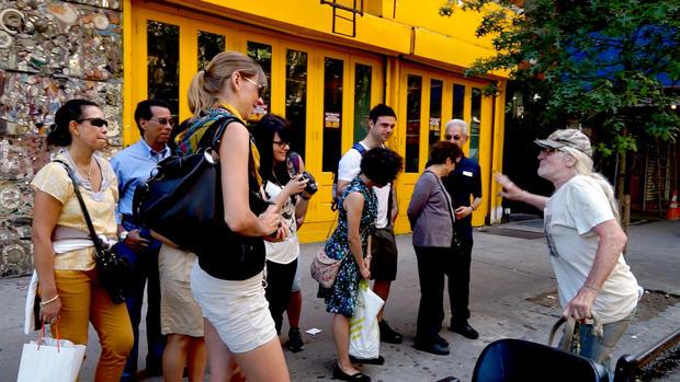 Jim Power与东村A大街的一群游客交谈。