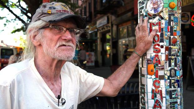 Jim Power站在东村圣马克广场的一个灯柱马赛克旁边。