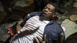 A policeman lies injured on the ground after clashing with demonstrators during a protest in Rio de Janeiro, Brazil, Monday, June 17, 2013.