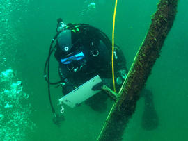 French underwater archaeologist Olivia Hulot jots notes while inspecting a timber jutting from the bottom of northern Lake Michigan.
