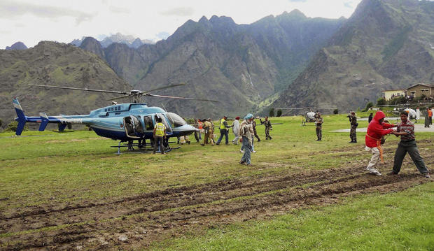 Rescuers help escort stranded pilgrims to helicopters to evacuate at Joshimath in the northern Indian state of Uttarakhand, India.