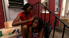 Two Baltimore residents sit on the stoop of an abandoned home.