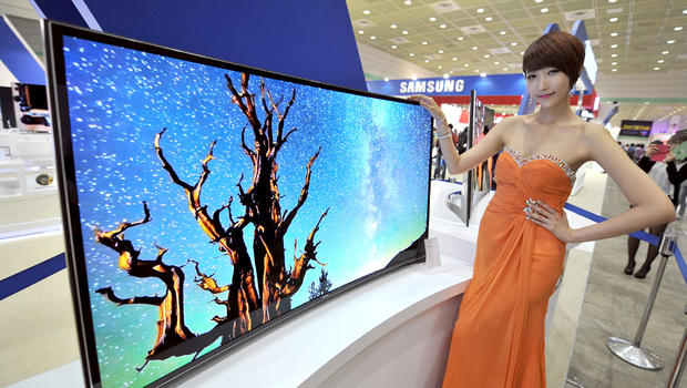 A South Korean model poses with a 55-inch curved OLED TV of Samsung Electronics during an IT show in Seoul on May 21, 2013.