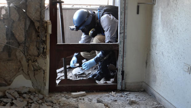 A United Nations arms expert collects samples at the site of an alleged chemical weapons attack in Damascus' eastern Ghouta suburbs