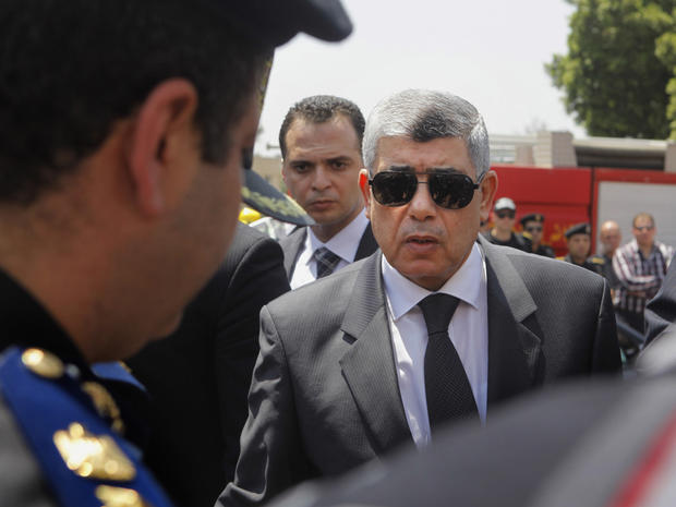 Egyptian Interior Minister Mohammed Ibrahim, right, gives his condolences to a policeman during a military funeral in Cairo, Egypt. Aug. 15, 2013.