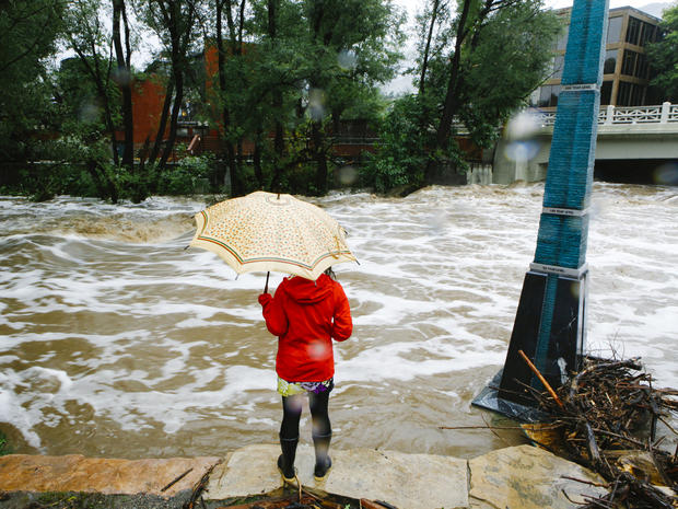 A woman looks at Boulder Creek, which flooded early Sept. 12, 2013, after three days of heavy rainfall in Boulder, Colo.