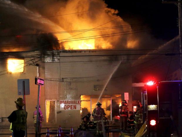 消防队员于2013年9月12日星期四在新泽西州海滨公园的海滨公园木板路上的一座建筑物中大火大火。在木板人行道的海滨公园区域的一个冷冻蛋羹架上开火,并迅速向北蔓延到邻近的海滨高地。