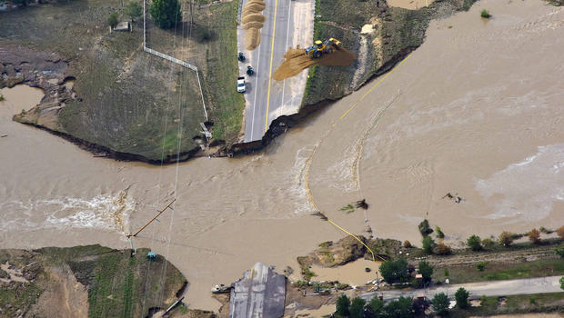 A road crew works on a stretch of highway washed out by flooding along the South Platte River in Weld County, Colorado near Greeley, Saturday, Sept. 14, 2013. Hundreds of roads in the area have been damaged or destroyed by the floodwaters that have affected parts of a 4,500-square-mile area.
