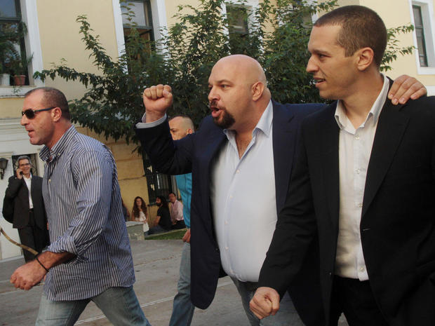 Lawmakers of the extreme far-right Golden Dawn party, Ilias Kasidiaris, right, Ilias Panayiotaros, center, and Nikos Michos, left, leave a court after after judicial authorities' decision to release them
