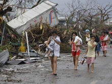 Residents shield their noses from the smell of dead bodies in Tacloban city