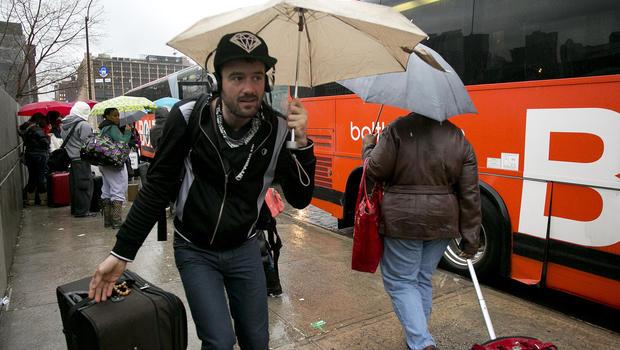 Passengers board a BoltBus during a light rain Nov. 27, 2013, in New York.