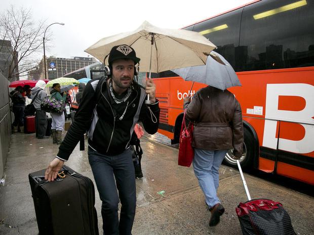 乘客在2013年11月27日的小雨中登上BoltBus,在纽约。